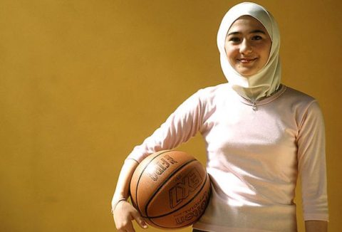 Image Veiled Jordanian Muslim girl with basketball in Amman gym.